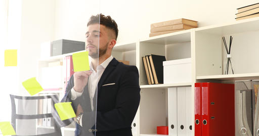 businessman in suit coat removing stickers from glass wall Footage