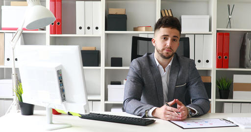 young businessman in workplace looking at camera Live Action