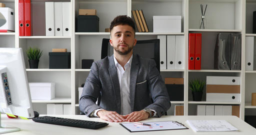 businessman in gray jacket sitting at table in white office and looking at Live Action