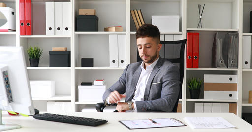 young businessman in gray jacket sitting at table in white office, looking at Live Action