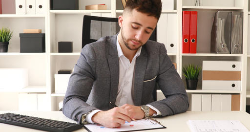 businessman in gray jacket sitting at table in white office and writing on Live Action