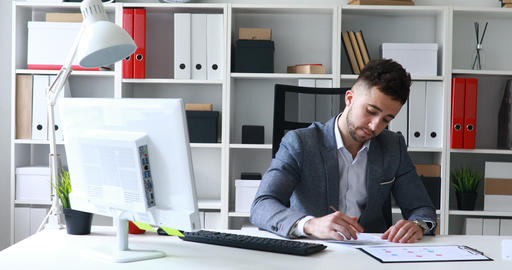 businessman in gray jacket sitting at table in white office, signing document Live Action
