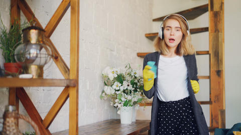 Creative young blonde is dusting table with cloth, listening to music with Footage