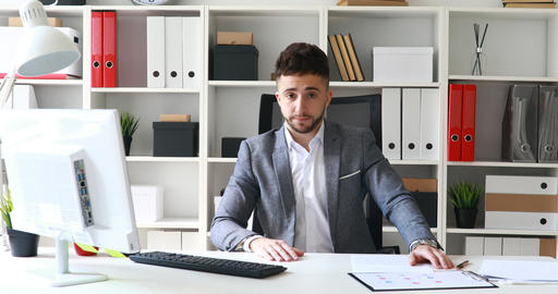 businessman in gray jacket sitting at table in white office and shaking head Live Action