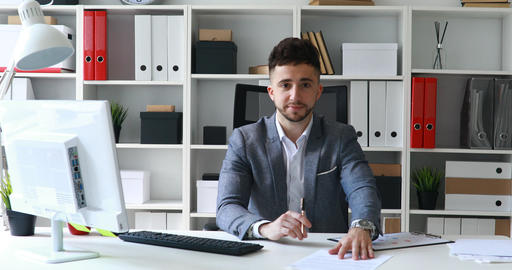 young man gray jacket sitting at table in white office and offering documents Live Action