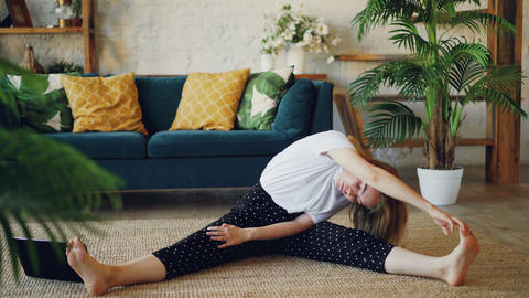Flexible blonde is doing stretching exercises at home sitting on floor in modern Footage