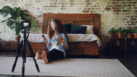 Young lady is recording video for online vlog showing smartphone and photographs Live Action