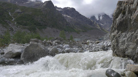 A fast mountain river runs into a ravine among the rocks Footage