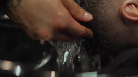 A young guy gets a haircut and hair care service from a bearded man with a hair Footage