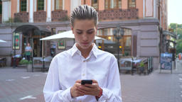 Young modern woman is standing on street and waiting for someone, typing message Footage
