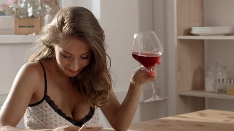 Sexy and attractive woman in candid dress sits at the table in a cafe, drinks Footage