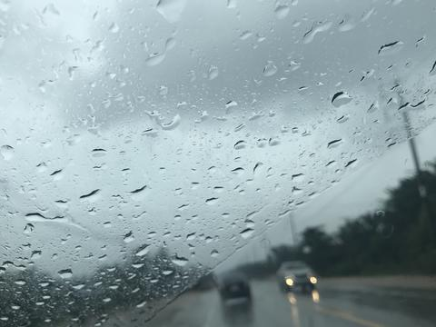 countryside road view from car's front windscreen which focus on raindrops Photo