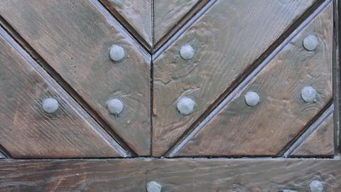 Rustic brown wooden door texture. Fragment of wooden door with metal rivets. Live Action