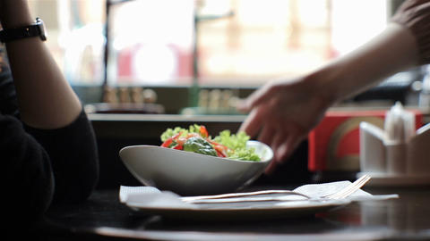 Waiter in a restaurant brings a delicious fresh salad dish to the table Footage