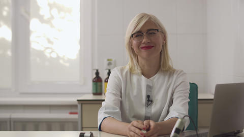 Beautiful dermatologist girl gives an interview at the workplace Live Action