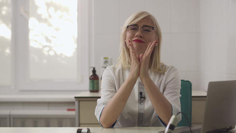 Beautiful dermatologist girl gives an interview at the workplace Footage