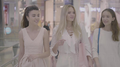 Happy young girls friends walking in shopping mall Footage