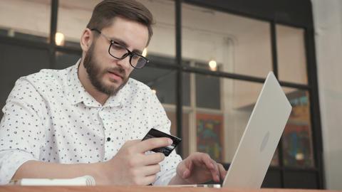 Man paying online by bank card at laptop GIF