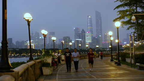 People walking on the embankment in evening city ビデオ