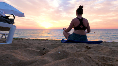 Peace and relaxation while woman is doing yoga on the beach Footage