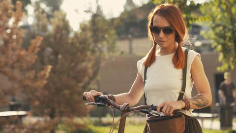 Woman walking beside riding bicycle on city park. Woman bike park Photo