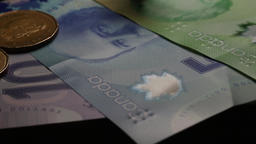 Canadian coins spinning and falling onto paper money bills. Gold one dollar Footage