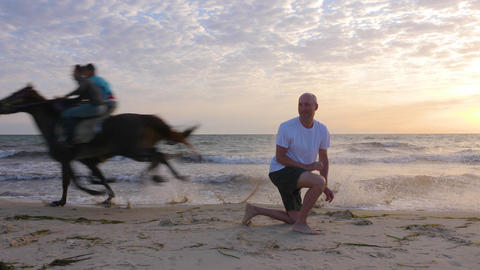 Sportsman exercising on seashore while mad riders running on horses near him GIF