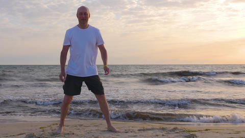 Sportive man stretching leg on seashore with waves at sunrise Live Action