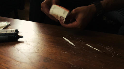 A man trying his fist line of cocaine, rolling a bill alone 4K Footage