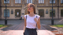 Nice young woman leaves university, walks along in park in daytime in summer Footage