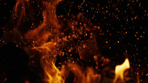 Fire sparks moving on dark at black background coming from brightly burning warm ビデオ