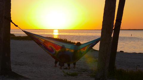 Girlfriends watching sunset on rainbow hammock Live Action