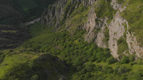 Flying above green gorge between rocky slopes of armenian mountains. Sunset time Footage