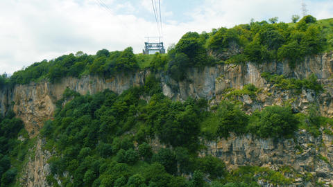 Moving on cableway above steep rocky wall towards aerial tram station in Live Action