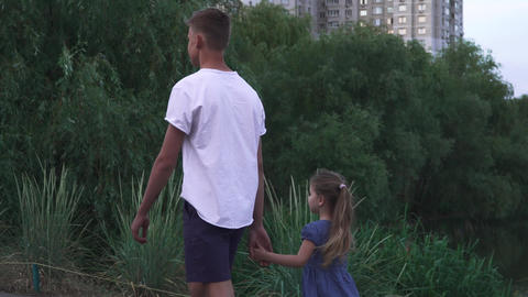 Brother and sister are walking near the river together Footage
