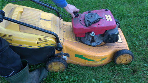 Gardener manually starting old lawn mower in garden on grass Live Action