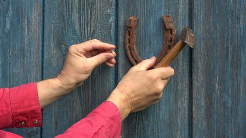Hammering hanging old rusty horseshoe on blue wooden door with hammer Footage