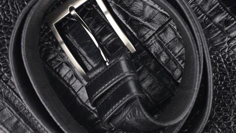 Rotation, close-up of a black belt, lying on a black crocodile skin Footage