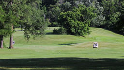 Golf cart driving down a green fairway with hills and trees. Golfers drive to Footage