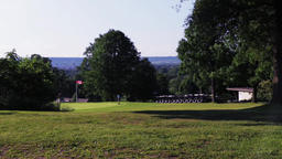 Wide establishing shot of a golfer teeing off on a green fairway with golf carts Footage