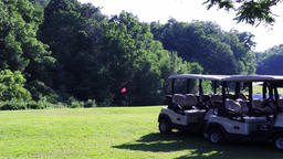 Wide establishing shot of an empty golf course with trees, golf carts, and flag Footage