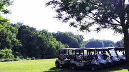 Golf carts lines up along a fairway at a local golf course. Establishing shot f Footage