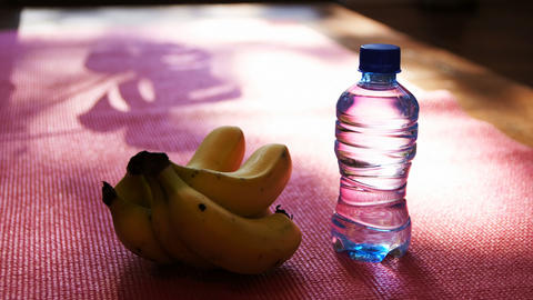 Banana and water bottle on exercise mat at home 4k Live Action