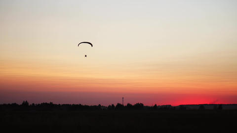 The pilot on a paraglider flies from the camera gradually moving away into the Live Action