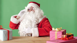 Satisfied Santa Claus speaks on the phone, laughs, sits at table with gifts Footage