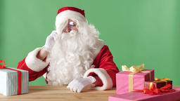 Evil Santa Claus speaks on the phone, beats his fist on table, sits at table Footage