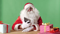 Smiling Santa Claus showing tablet with blue screen in camera, gifts on the Footage