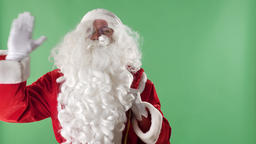 Santa Claus enters the frame with a bag, look at the camera and waving his hand Footage