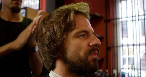 Barber applying hair wax on mans hair 4k Footage