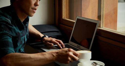 Man having coffee while using laptop 4k Footage